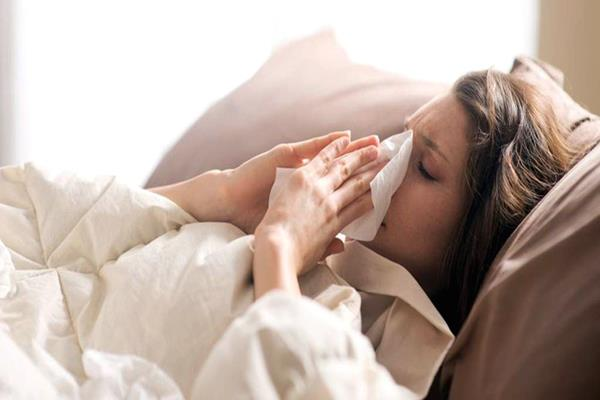 Sick Woman Blowing Her Nose While In Bed